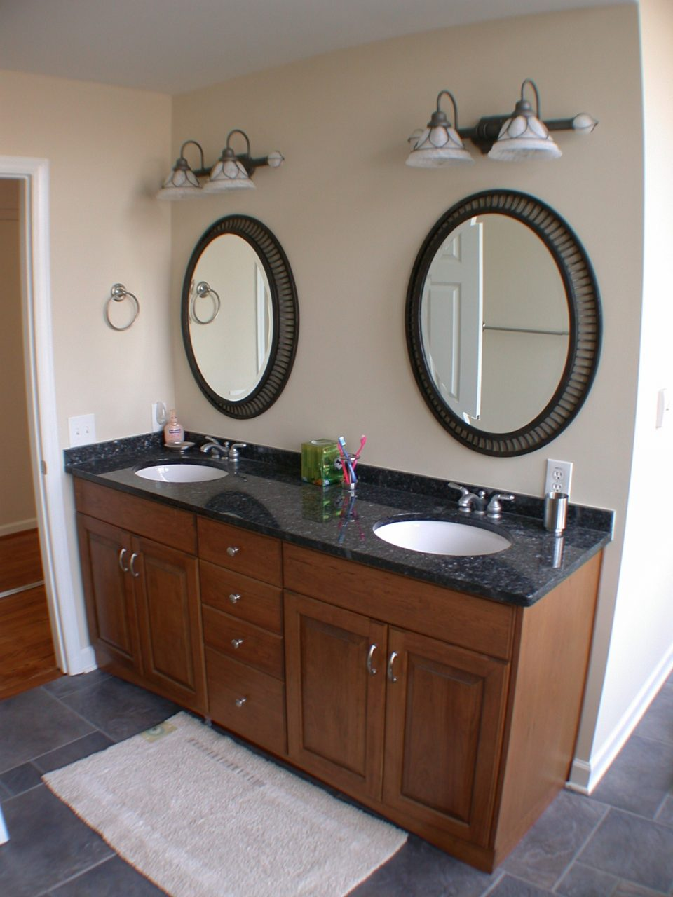Brown Wooden Bathroom Vanity With Double Circle White Sinks And