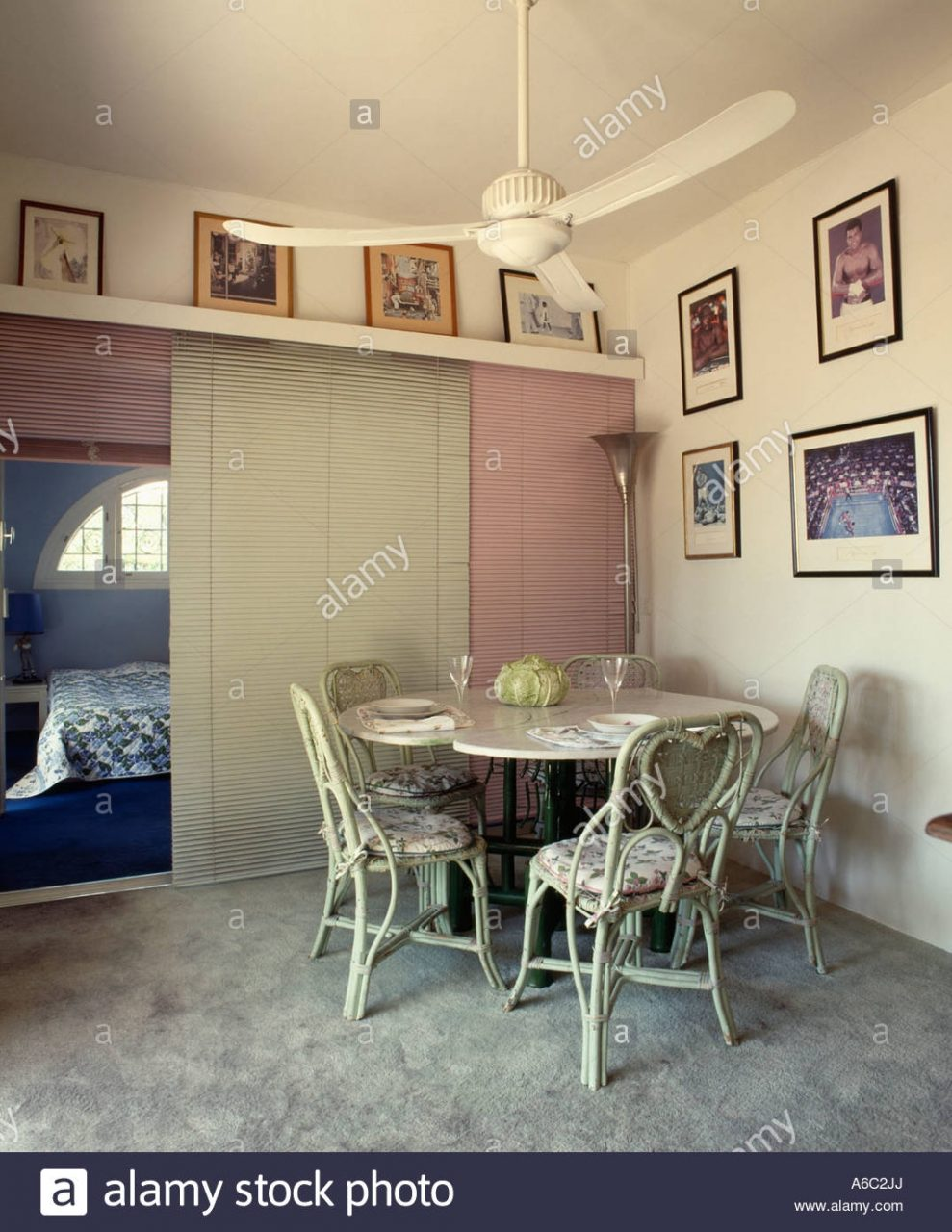Ceiling Fan Above Circular Table In Dining Room With Pictures On
