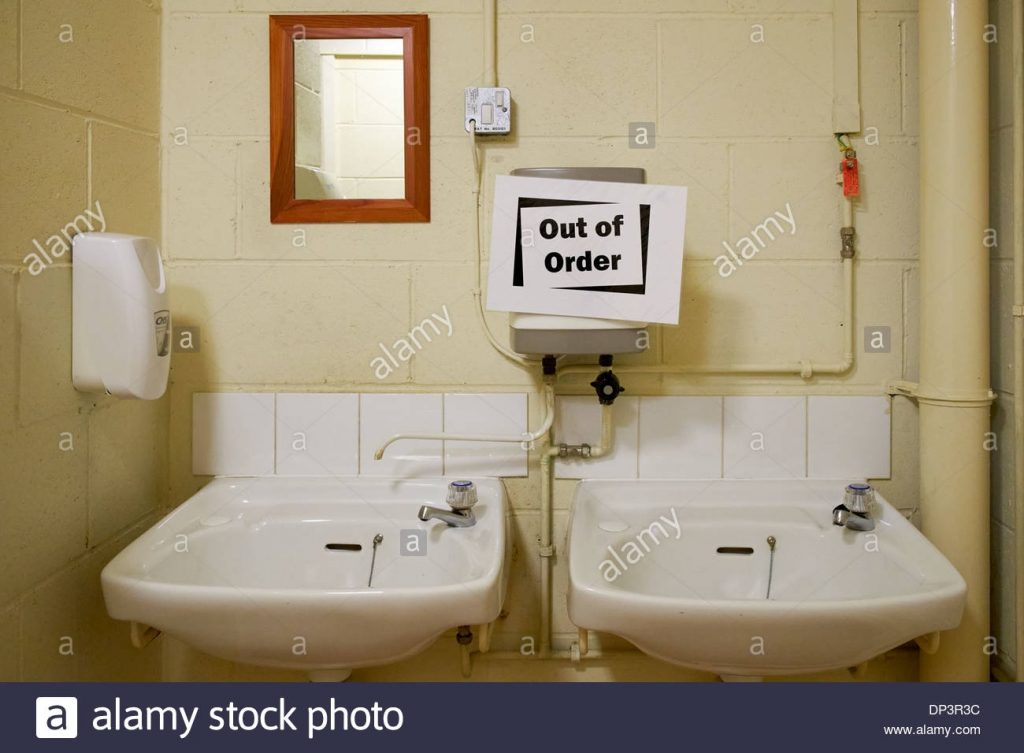 Out Of Order Sign On Hot Water Heater Above Washbasins In Toilet
