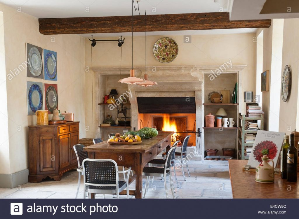 Provencal Kitchen With Large Stone Fireplace And Wooden Dining Table
