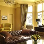 Brown Couch With Yellow Walls For Trendy Living Room Decorating