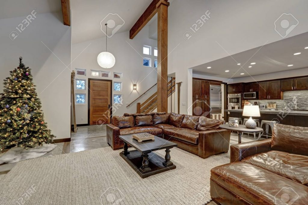 Vaulted Ceiling Living Room Accented With Wood Beams Over Brown