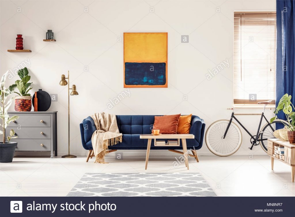 Yellow And Blue Painting Hanging On White Wall In Bright Living Room