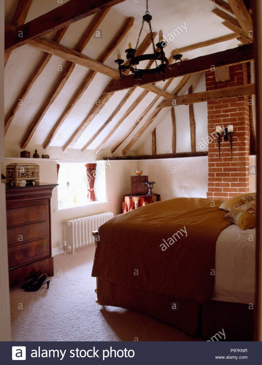 Brown Throw On Bed In Cottage Bedroom With Beamed Apex Ceiling Stock
