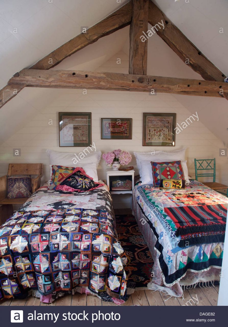 Colorful Patchwork Quilts On Twin Beds In Cottage Bedroom With