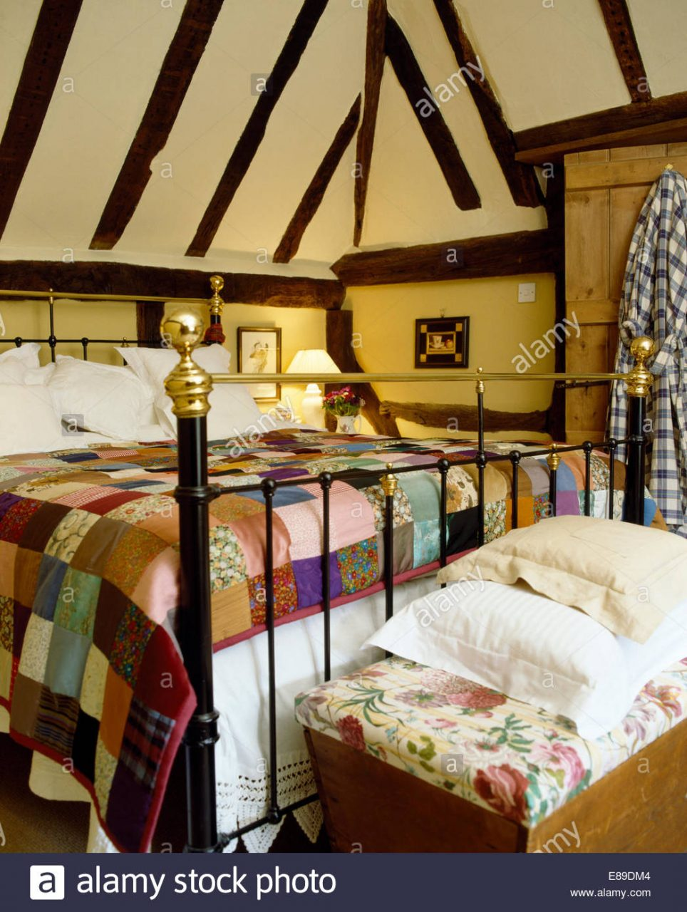 Colourful Patchwork Quilt On Antique Brass Bed In Cottage Bedroom