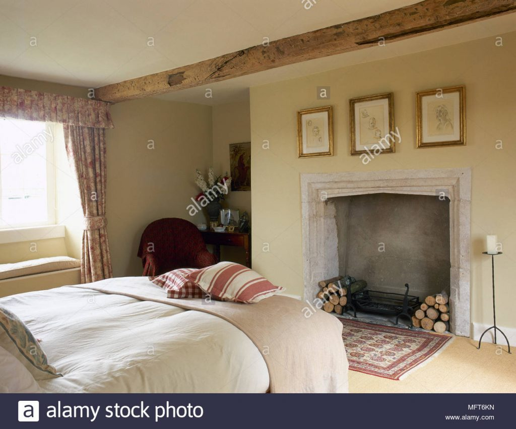 Country Cottage Bedroom With A Beamed Ceiling Stone Fireplace With