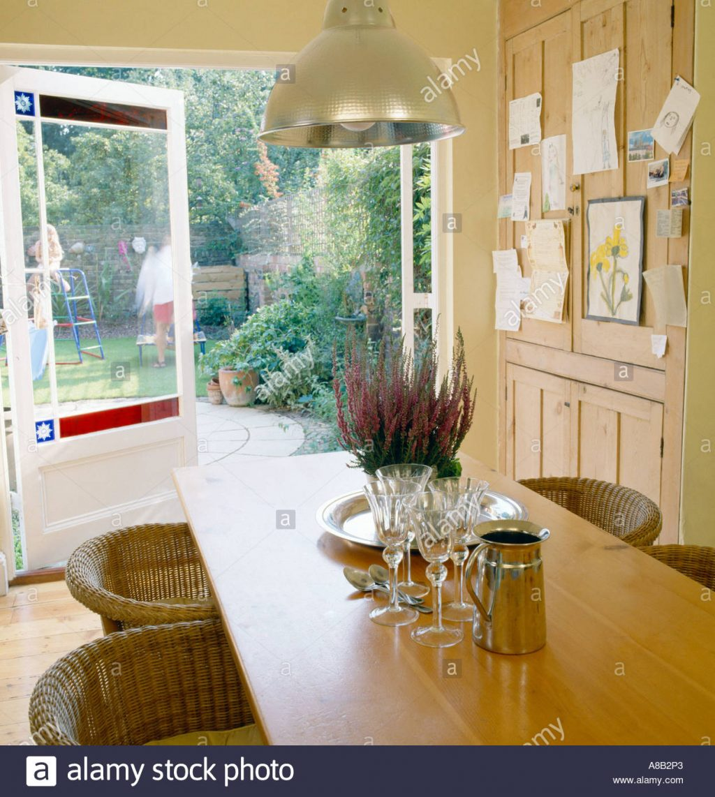 Kitchen Table In Kitchen With French Doors Leading To Garden Stock