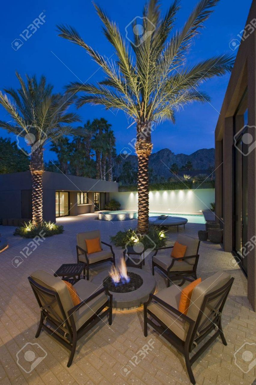 Lit Palm Trees At Firepit With Chairs On Terrace Of California