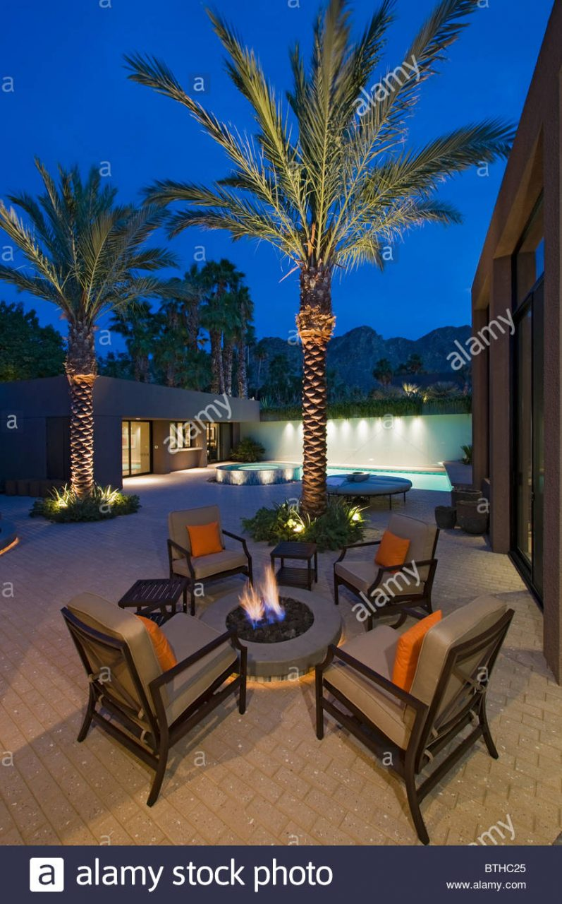 Lit Palm Trees At Firepit With Chairs On Terrace Of California Home