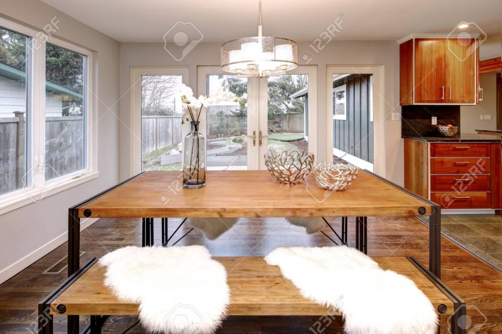 Spacious Dining Room With Wooden Dining Table And French Doors To