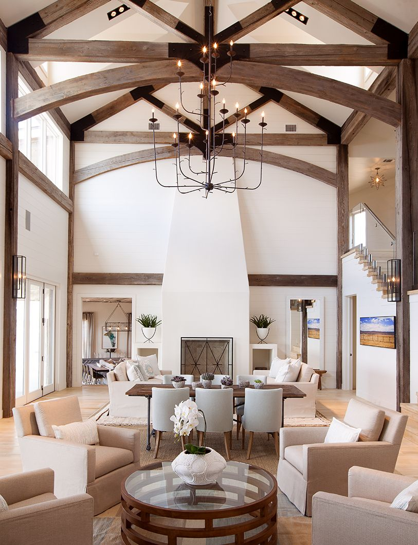 High Ceilinged Great Room With Dark Wood Exposed Beams And Neutral