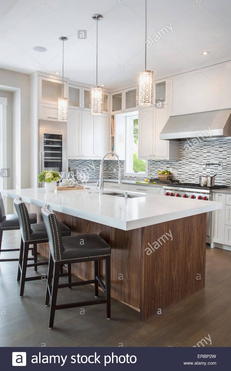 Pendant Lights Over Modern White Kitchen Island Stock Photo