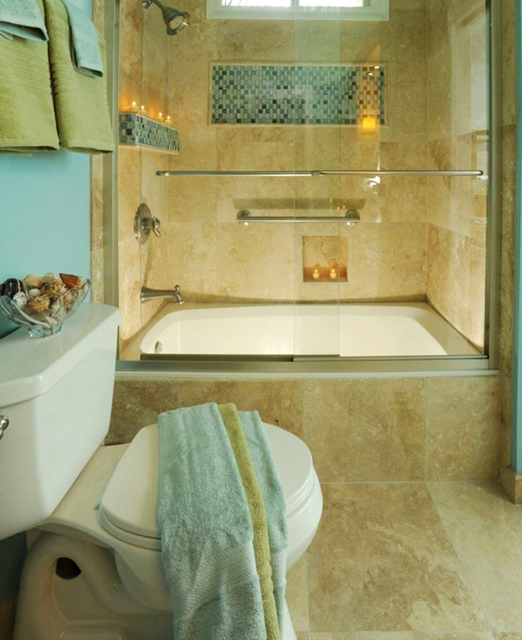 A Travertine Tile Shower With Glass Mosaic Accent Is The Highlight