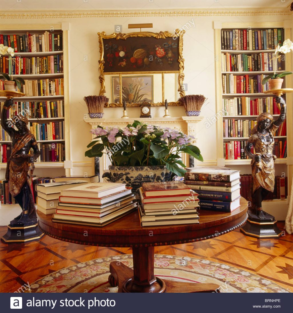 Books In Piles On Circular Antique Table In Library Dining Room With