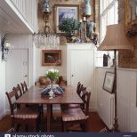 Chandelier Above Antique Table And Chairs In Small White Paneled