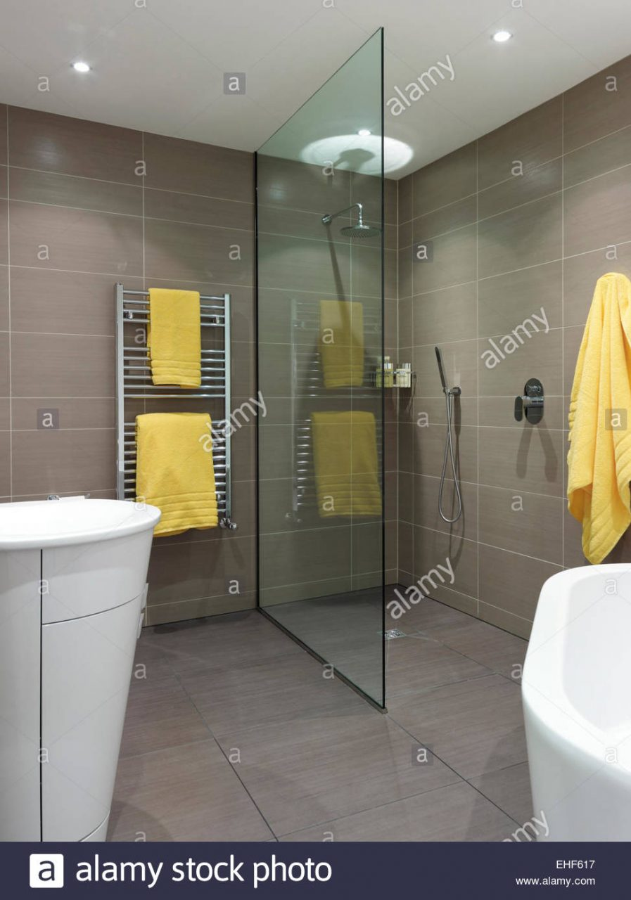 Glass Divider And Towel Rail With Yellow Towels In Bath And Shower