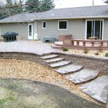 Large Stone Retaining Wall With Patio And Sitting Stones Oasis