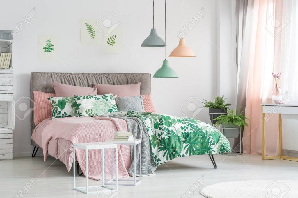 Pastel Bedding On Stylish Bed In White Bedroom With Plants Stock