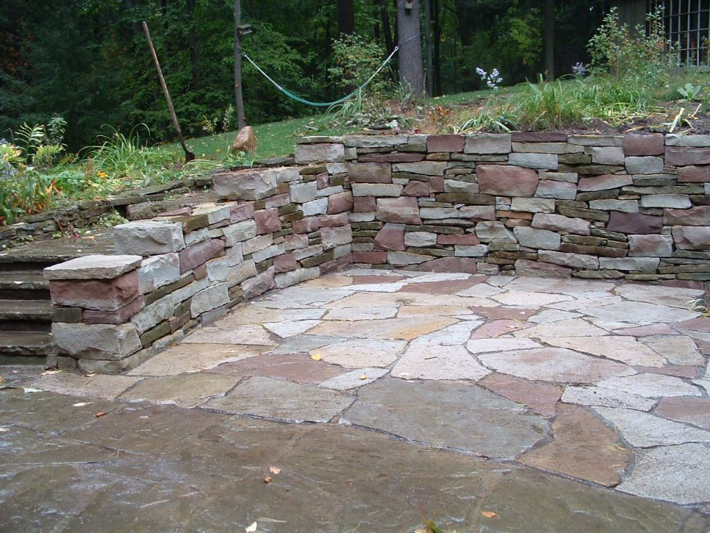 Patio Designs Among Retaining Walls Matched With Stone Flooring
