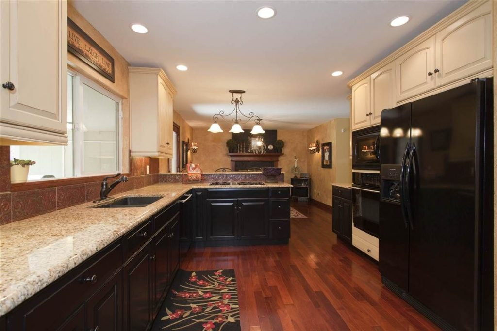 Pretty Kitchen With Light Upper Cabinets And Light Granite With Dark