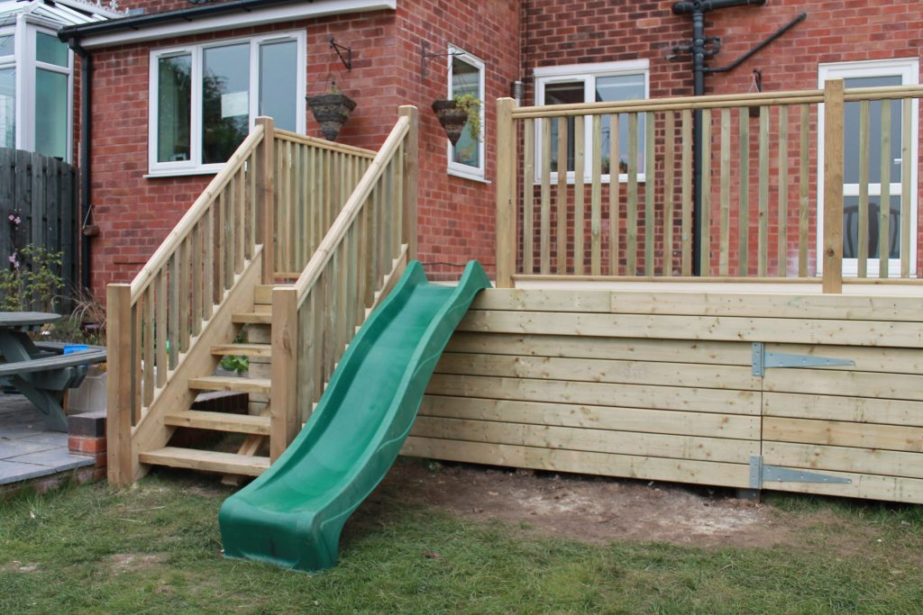 Raised Decking With Childrens Slide Play Area Completed In