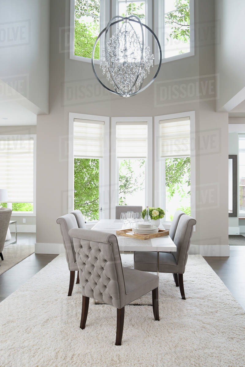 Vaulted Ceiling Chandelier Hanging Over Elegant Dining Table Stock