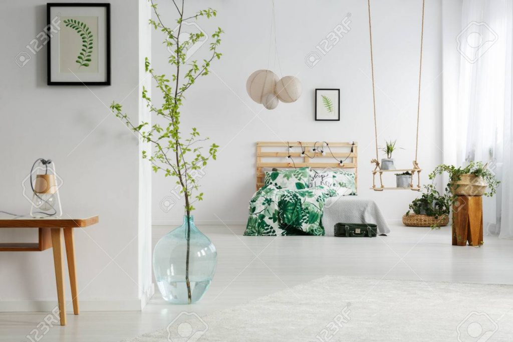 White Bedroom With Green Plants Wooden Bed And Swing Stock Photo
