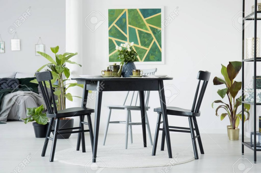 Black Chairs At A Table With White Roses In Dining Room Interior