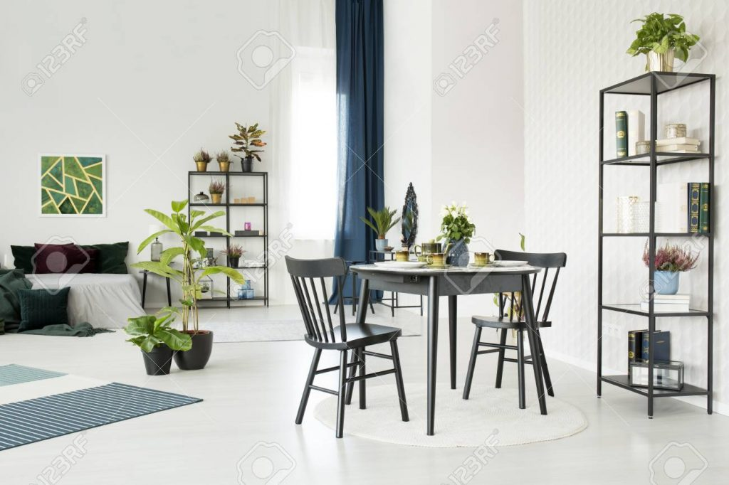 Black Dining Table In Open Space Interior With Plants And Bed