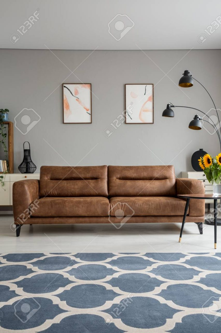 Blue Patterned Carpet And Leather Sofa In Grey Living Room Interior
