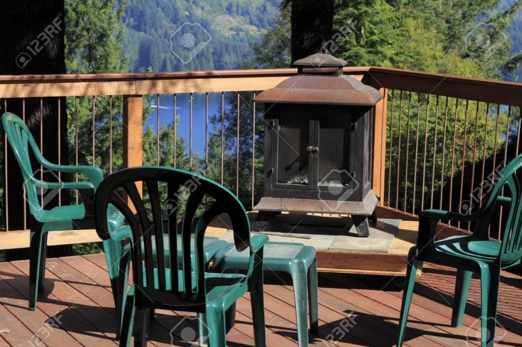 Four Plastic Chairs On A Scenic Sunny Outdoor Deck With A Fireplace