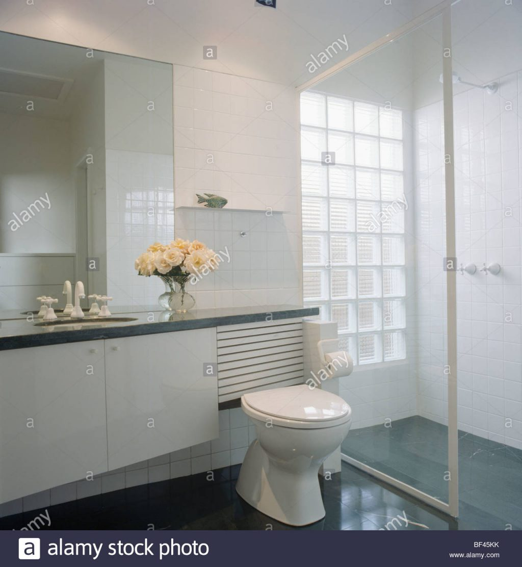 Glass Door On Walk In Shower In Modern White Bathroom With Glass