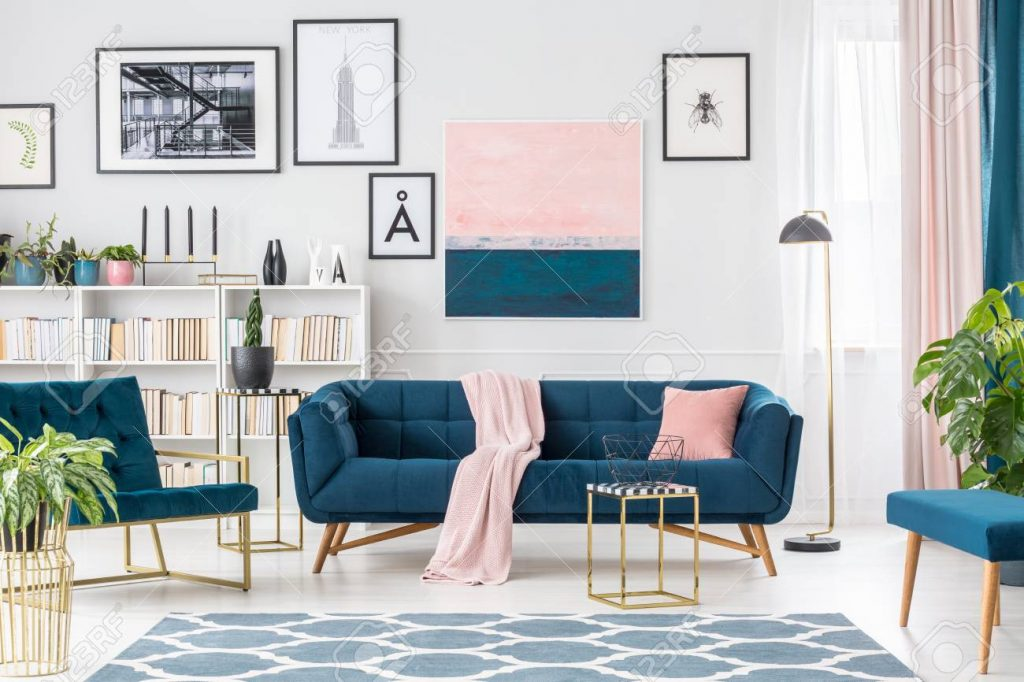 Gold Table In Front Of A Navy Blue Couch With Pink Blanket In