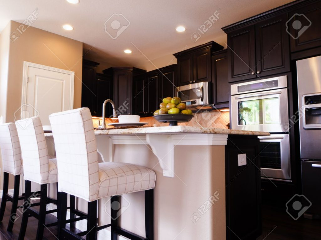 Modern Kitchen With Dark Wood Cabinets And Hardwood Floors Stock