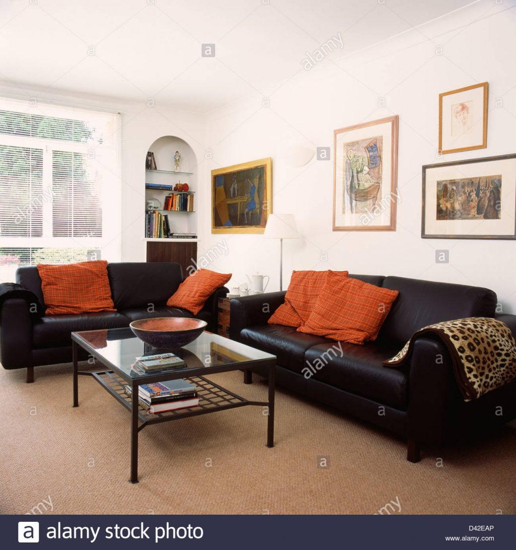 Orange Cushions On Black Leather Sofas In Living Room With Beige