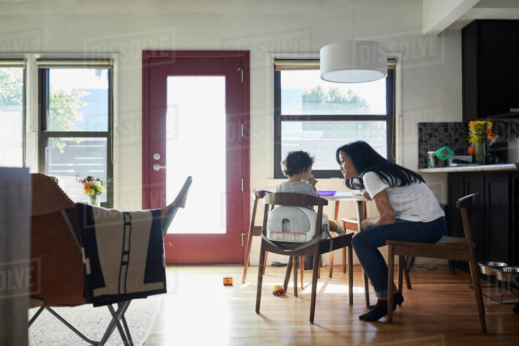 Side View Of Mother Talking With Son Sitting On Chair In Living Room