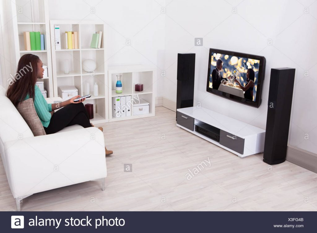 Side View Of Young Woman Watching Tv In Living Room Stock Photo