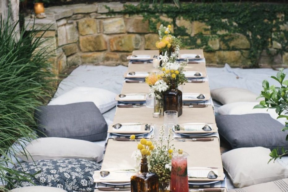 The Long Picnic Table Setting With Floor Cushions Rugs And Festoon