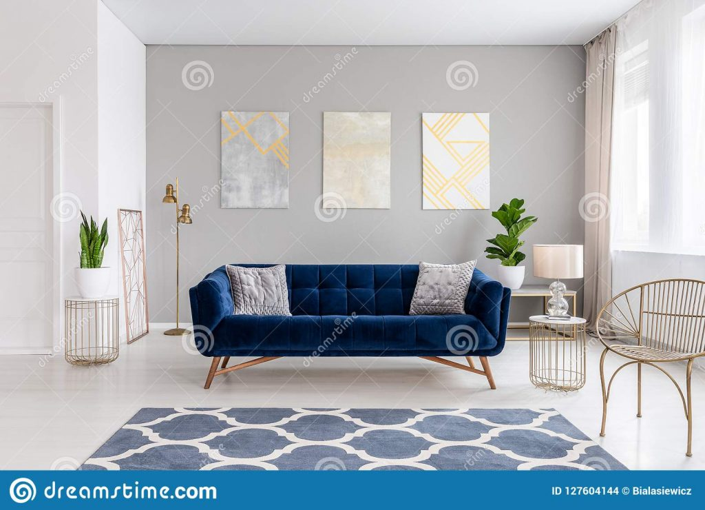 An Elegant Navy Blue Sofa In The Middle Of A Bright Living Room