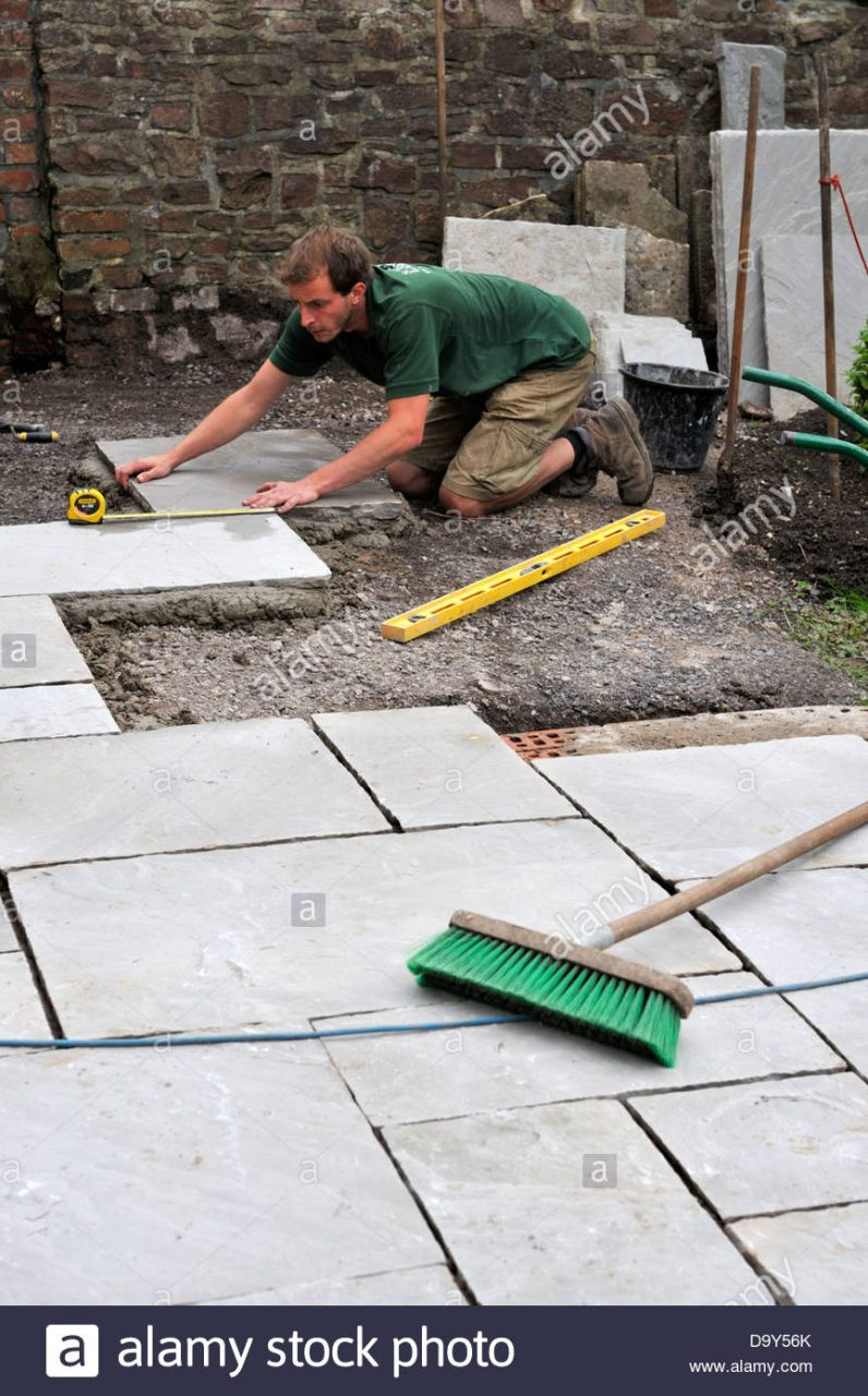 Construction Of A Patio Laying Natural Stone Paving Man Measuring