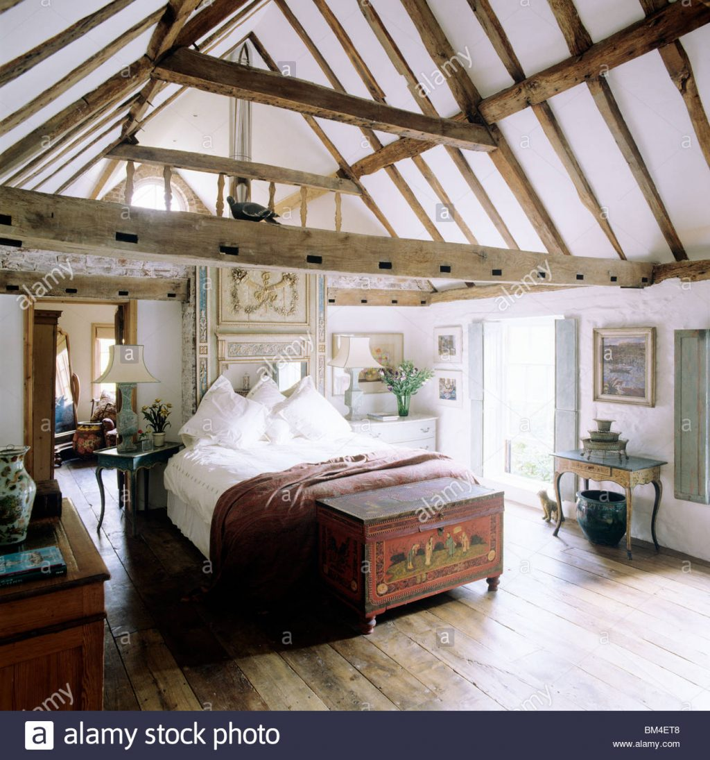 Country Bedroom With Pitched Ceiling And Beams With Wooden Floor And