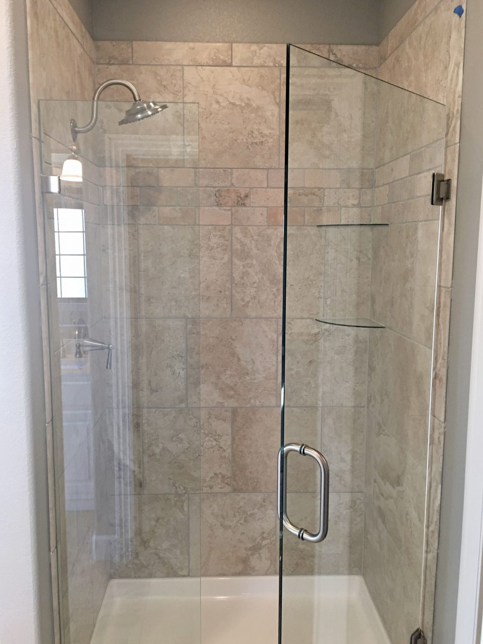 Glass Door Shower With Greige Porcelain And Travertine Tile Walls