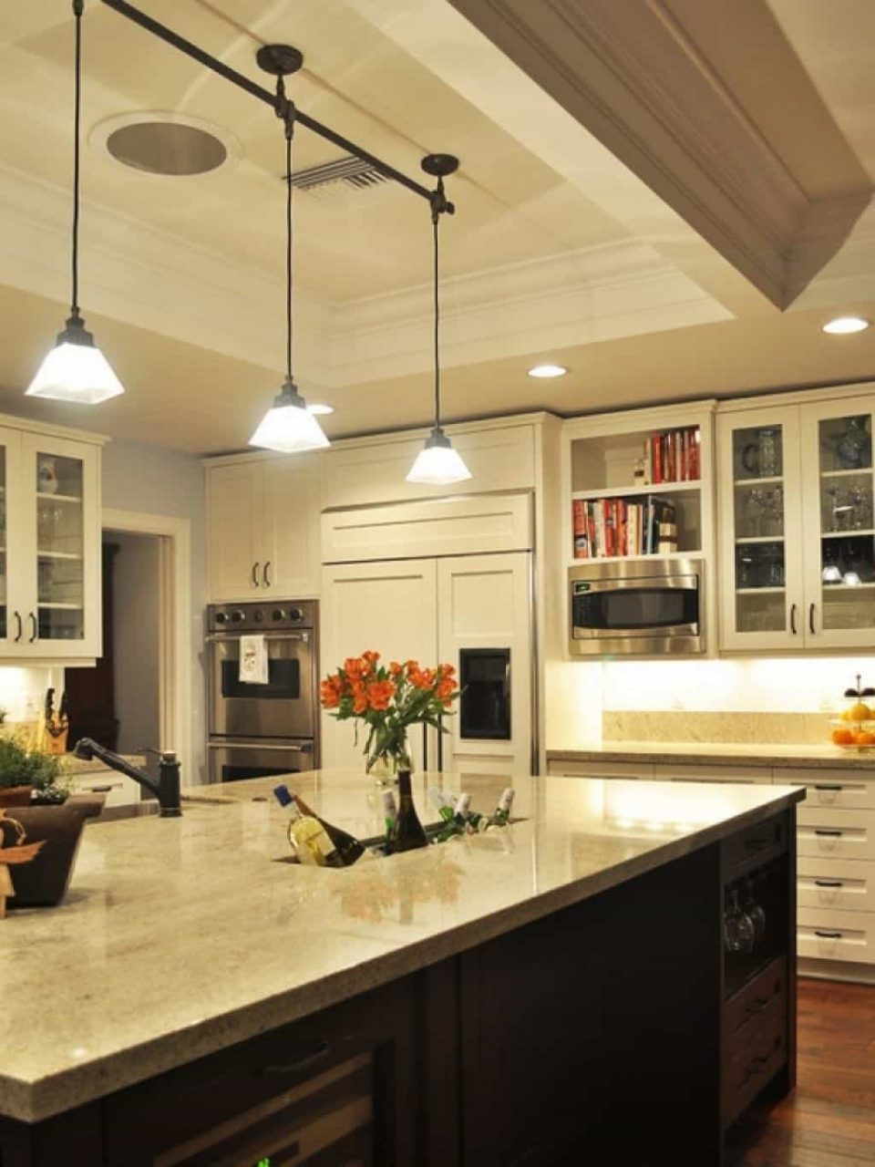 Kitchen With Wooden Cabinets And Pendant Track Lighting Stylish