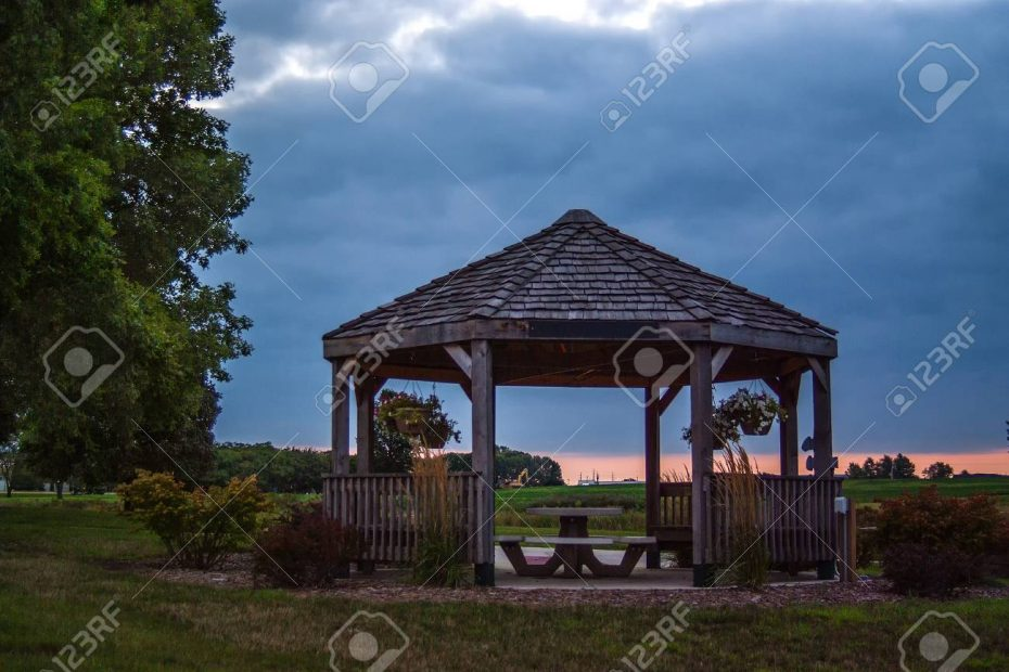 Large Rustic Gazebo With A Picnic Table In The Center Stock Photo
