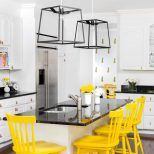 White Kitchen With Bright Yellow Stools And Flowers Add Color To A