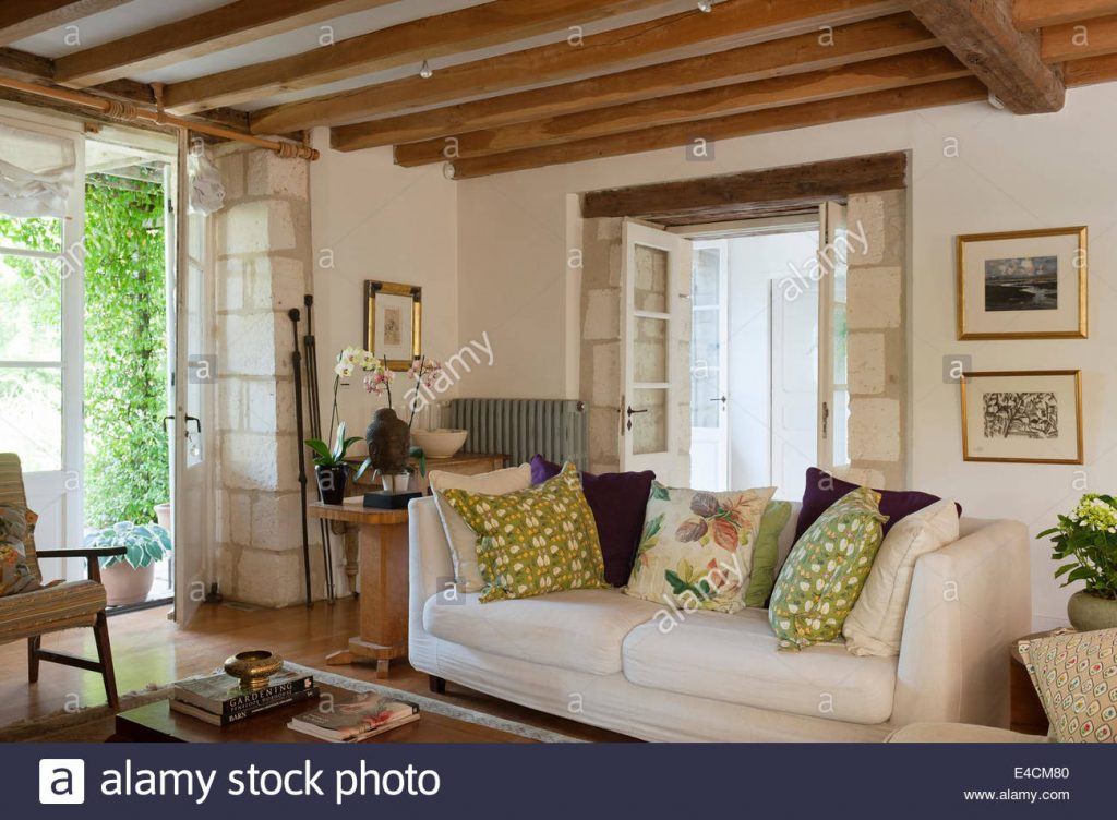 White Sofa In Living Room With Wooden Ceiling Beams And Stone Wall