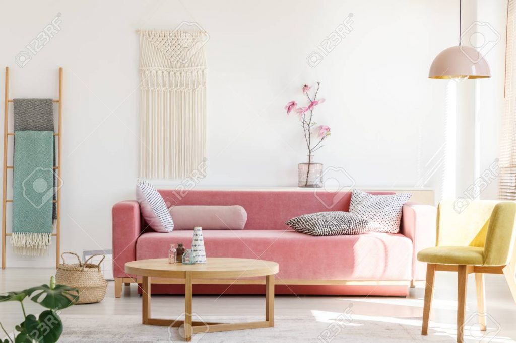 Yellow Chair Next To Pink Sofa And Wooden Table In Pastel Living