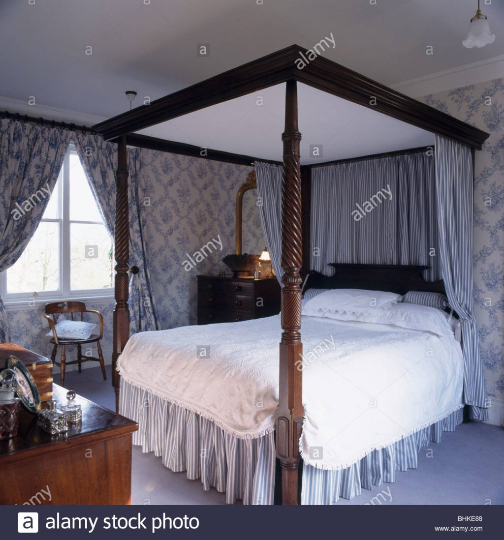 Four Poster Bed With Pastel Blue Drapes And White Bedlinen In