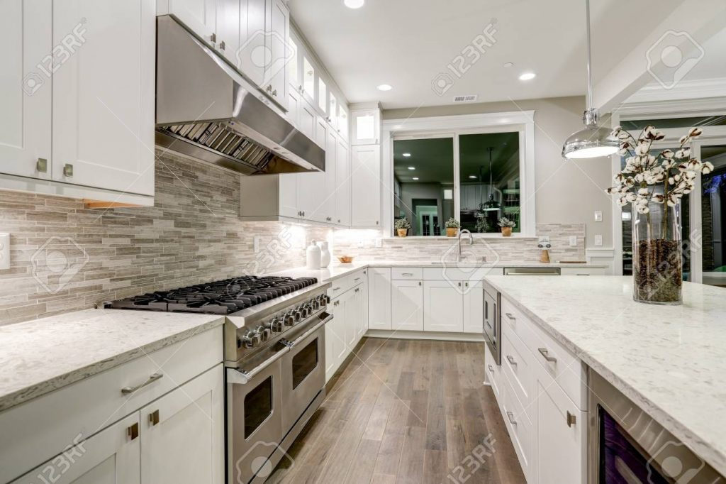 Gourmet Kitchen Features White Shaker Cabinets With Marble